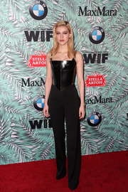 Nicola Peltz teamed her tough-chic top with a pair of black slacks.
