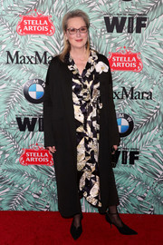 Meryl Streep topped off her dress with a simple black coat.
