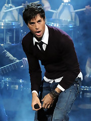 Enrique looks preppy perfect in a burgundy v-neck sweater worn over a white button down and black tie.