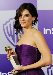 Sandra sports these dangling silver earrings on the red carpet, which really stand out against her deep purple strapless dress.