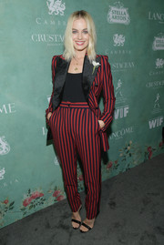 Margot Robbie kept it fun in a red and black striped pantsuit by Dolce & Gabbana at the Women in Film pre-Oscar party.