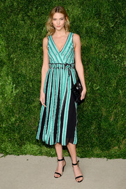 Karlie Kloss was all about easy sophistication at the CFDA/Vogue Fashion Fund Awards in a Proenza Schouler wrap dress rendered in aqua-blue and white stripes with sheer black inserts.