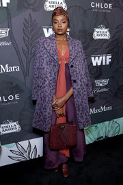 Kiki Layne looked chic in a purple leopard-print coat by Kate Spade at the Women in Film Oscar nominees party.
