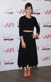 Lizzy Caplan's flared black Houghton skirt added a feminine touch to her look.