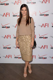 Sandra Bullock infused some elegance into her look via an embroidered nude pencil skirt by Burberry Prorsum.