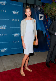 Karlie Kloss layered a gray cardigan over her lightweight dress for a bit of warmth.