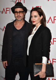 Angelina Jolie posed on the AFI Awards red carpet sporting and simple black leather clutch and pantsuit combo.
