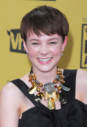 Carey was all smiles in an eclectic statement necklace and long black evening gown.
