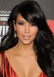 Kim Kardashian attended the Critics Choice Awards wearing cognac diamond slices with diamond earrings.