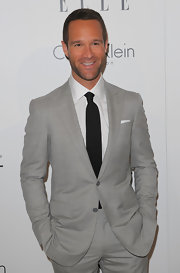 Chris looks classic and cool in a slate gray two-button suit with a white shirt and black tie.