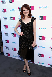 Ellie Kemper matched the Art Deco appeal of her dress with a thematic frame clutch.