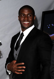 Reggie looks all class in this three piece suit with a contrast gray vest to accompany his black tie and suit.