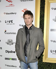 Chad wears a muted military inspired jacket with epaulets over a button-up and tie.