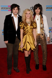 Kimberly Perry wears a gold cocktail dress with knee high boots to the AMA with her brothers.