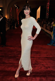 Sarah wears a bead saturated cream gown with a lovely curve hugging silhouette and front kick slit.