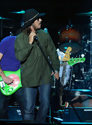 The rockstar paired his green button-down shirt with a wide-brimmed hat.