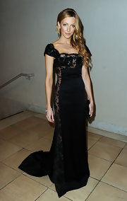 Katie wears an dramatic black evening dress with risque sheer side panel and bodice detailing.