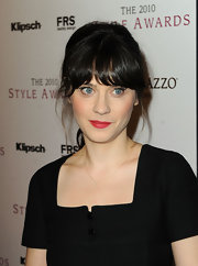 Zooey Deschanel vamped up her black dress with a matte application of red lipstick.