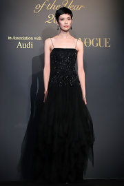 Tao wears a floor length black evening dress and shows off her elegant height.
