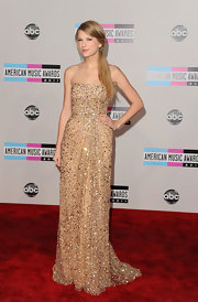 Taylor Swift dazzled at the 2011 AMAs. The country starlet was positively chic in a gold beaded dress that perfectly showed off her svelte figure. Taylor added green earrings for the perfect pop of color and a sleek side-ponytail to finish off the glamorous look.