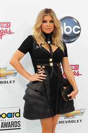 Fergie teamed her sultry bondage-inspired look with a tasseled skull clasp clutch.