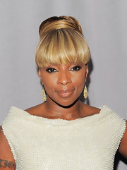 Mary. J Blige styled her hair in a classic bun that was fastened into place with her own tresses. Long bangs completed her elegant look.