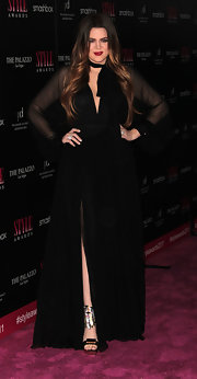 Khloe Kardashian donned an elegant black gown at the Hollywood Style Awards. She topped off her look with silver-accented platform sandals.