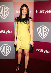 Shiri wore a muted yellow cocktail dress with a feathered neck piece.
