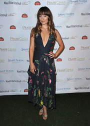 Olivia Wilde teamed her low-cut floral print dress with gold platform Tribute sandals.