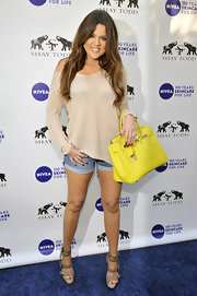 Khloe Kardashian spiced up her neutral summer look with a lemon yellow Birkin bag.
