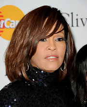 Whitney Houston wore her hair in a mid-length bob with side swept bangs.