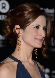 Livia Firth accented her navy dress with a pair of yellow gemstone cluster earrings.