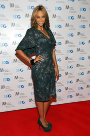 Tyra Banks smiled with her eyes while posign in this emerald print dress at the Matrix Awards.