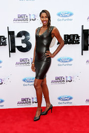 Lisa Leslie showed off her toned arms with this fitted black leather dress with gold studded detailing.