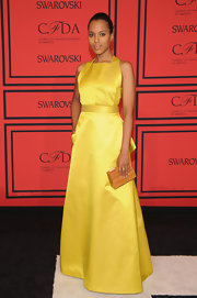 Kerry Washington stunned in a sunny yellow satin dress that featured a cinched waist, a criss-cross back, and a back ruffle detail.
