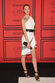 Candice Swanepoel chose this white dress that featured an embellished shoulder strap, a thick belted waist, and sequin-printed fabric panels.