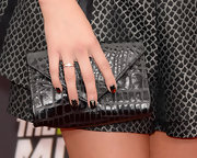 Alexa Vega paired a black snakeskin clutch with her edgy red carpet look.