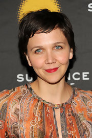 Maggie Gyllenhaal chose a vibrant red lipstick to add some color to her fair skin.