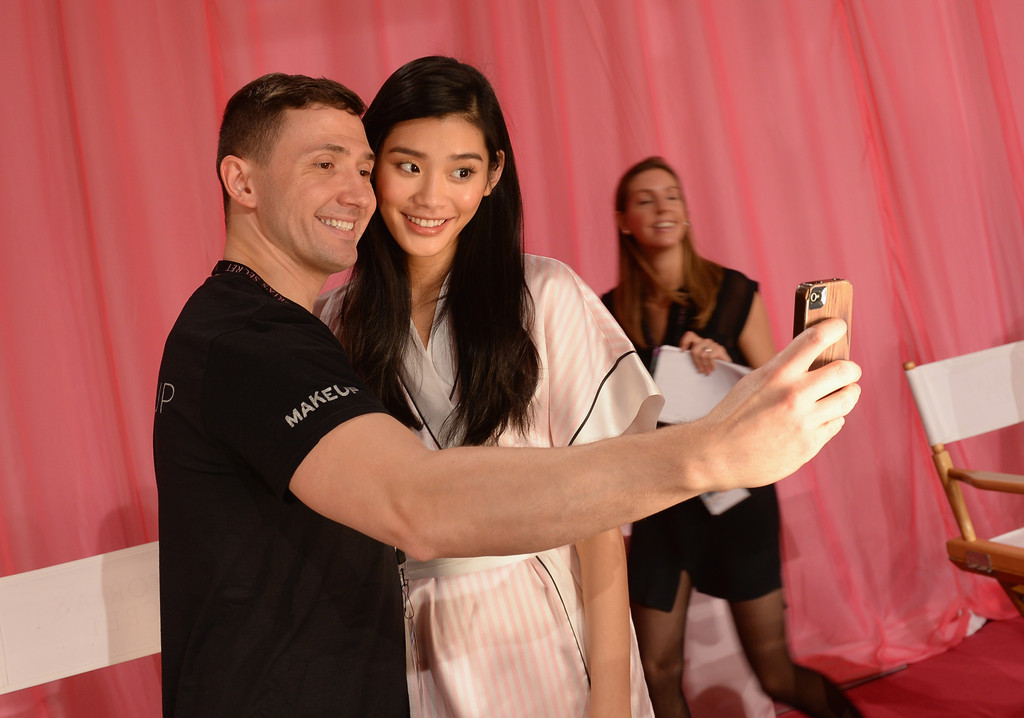 Model Ming Xi prepares at the 2013 Victoria's Secret Fashion Show hair and make-up room at Lexington Avenue Armory on November 13, 2013 in New York City.