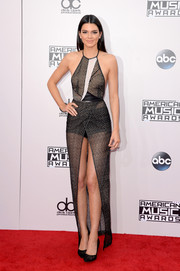 Kendall Jenner flaunted plenty of bare skin at the American Music Awards in a Yigal Azrouel monochrome halter dress made of see-through mesh fabric with a crotch-grazing front slit.