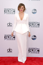 Ali Fedotowsky went for a futuristic vibe in a long-sleeve white peplum gown, complete with silver cuffs on both wrists, during the American Music Awards.