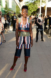Lupita Nyong'o looked exuberant in a low-cut mixed-stripe crop-top by Suno at the CFDA Fashion Awards.