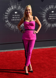 Gwen Stefani wore L.A.M.B. couture in a hot pink belted bustier top. She paired it with matching tuxedo stripe pants and black Louboutin pumps.