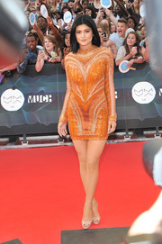 Kylie Jenner glittered at the MuchMusic Video Awards in an orange Nicolas Jebran mini featuring intricate beading and see-through panels.