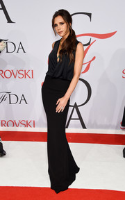Victoria Beckham opted for a simple black gown from her own line, featuring a draped wraparound bodice and a sleek skirt, for her CFDA Fashion Awards look.