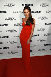 Victoria Beckham showed off her svelte physique in a red column dress with a strappy neckline during the Glamour Women of the Year Awards.