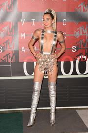 Miley Cyrus completed her racy look with silver thigh-high boots with gold platforms, also by Versace.