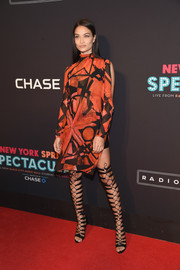 Shanina Shaik attended the New York Spring Spectacular wearing a bold orange and black print dress with a high neck and split sleeves.