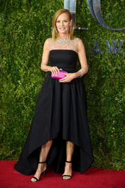 Marg Helgenberger injected a bright pop via a magenta satin clutch by Swarovski.
