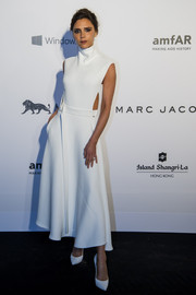 Opting for a monochromatic look, Victoria Beckham paired her dress with white pumps.